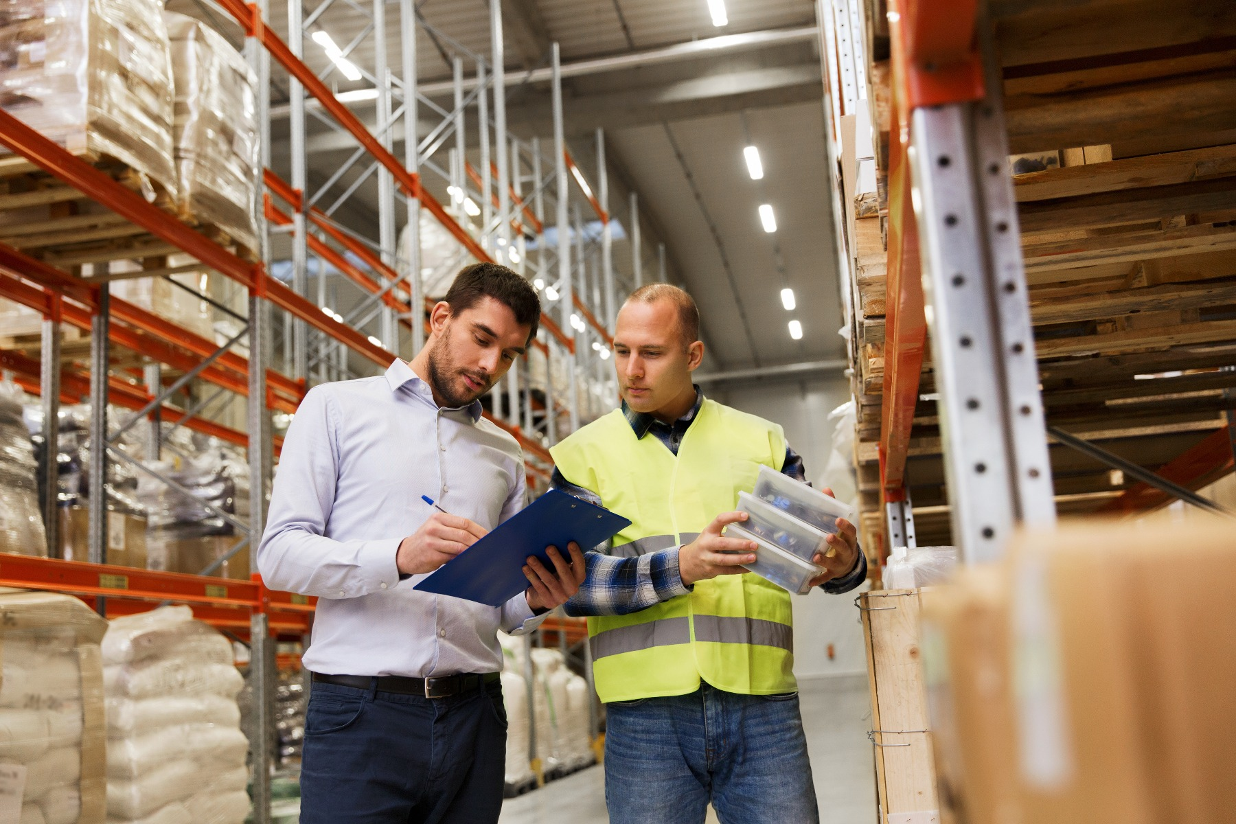 Two employees checking stock in warehouse