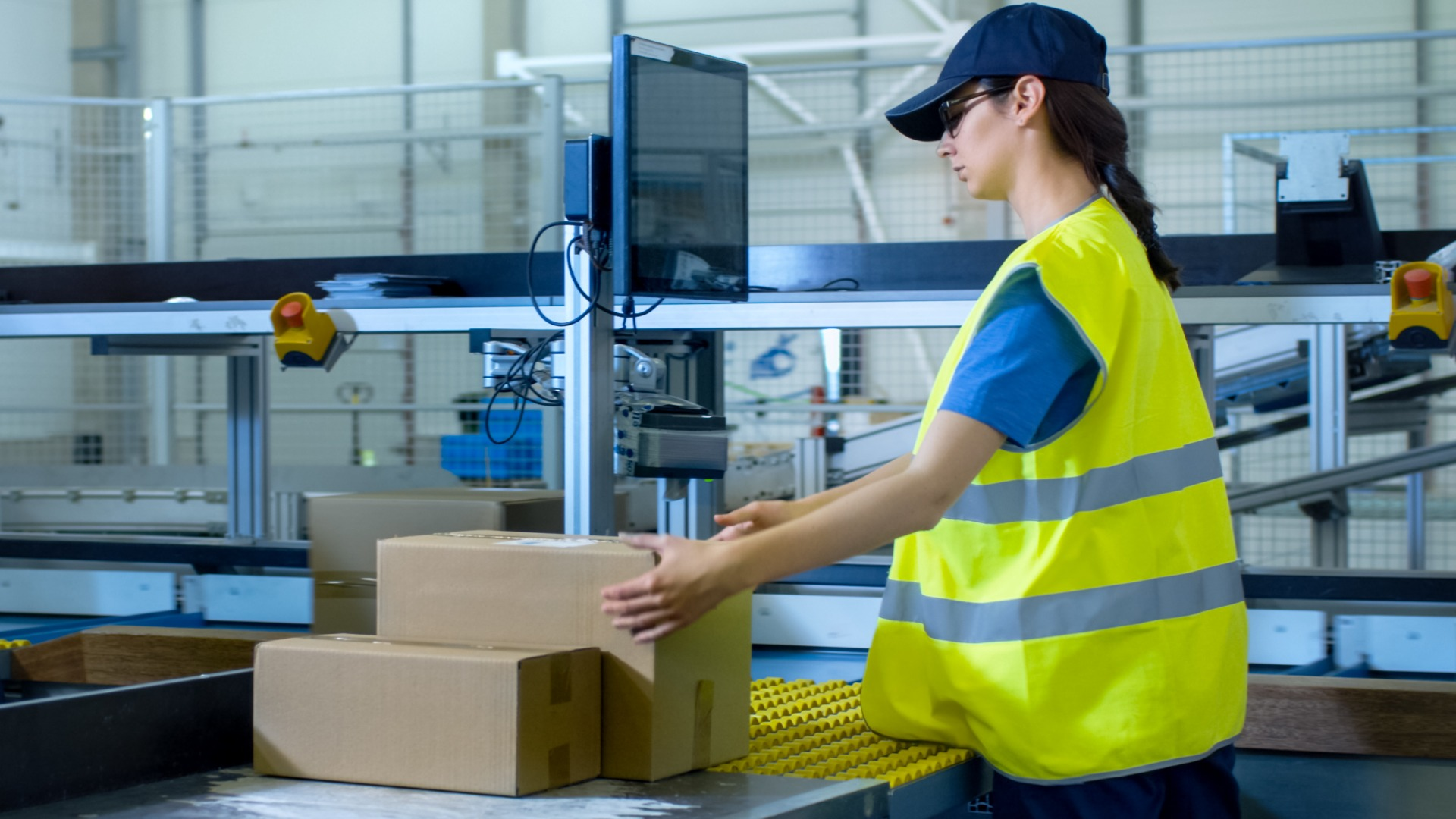 Woman boxing handling boxes in warehouse