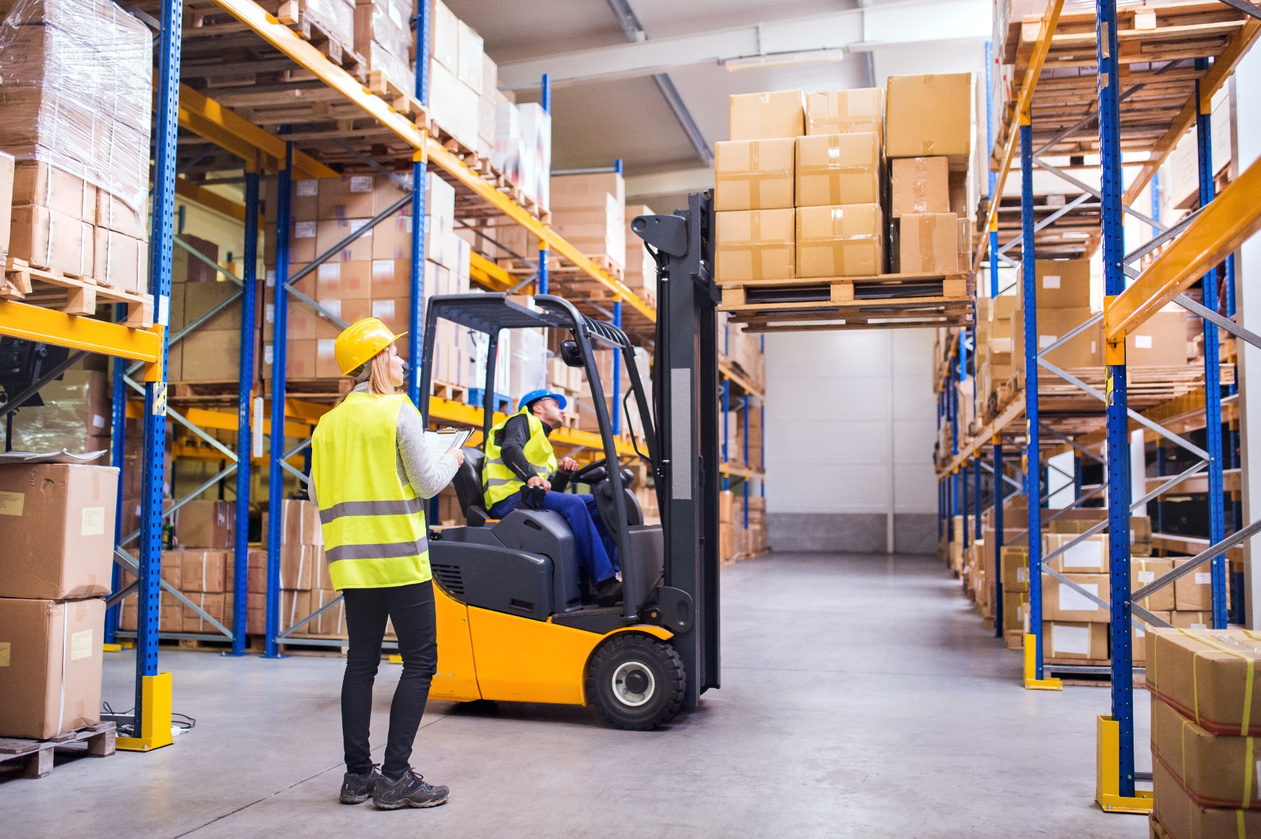 Man on forklift picking products in warehouse