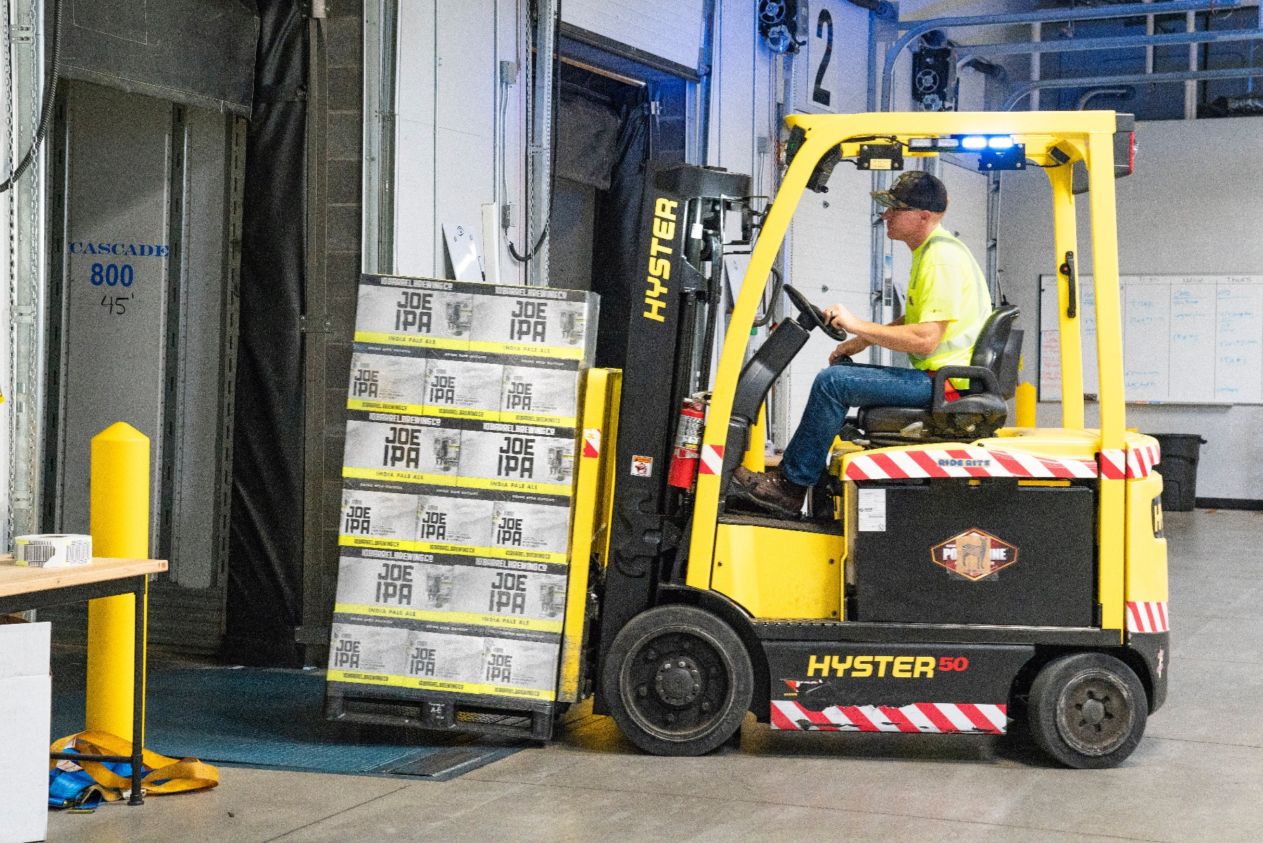 Forklift moving storage boxes in warehouse